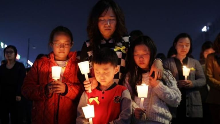 Students hold candles as they pray for the safe return of missing passengers who were travelling aboard south Korean ferry the Sewol. The death toll has climbed to 150.
