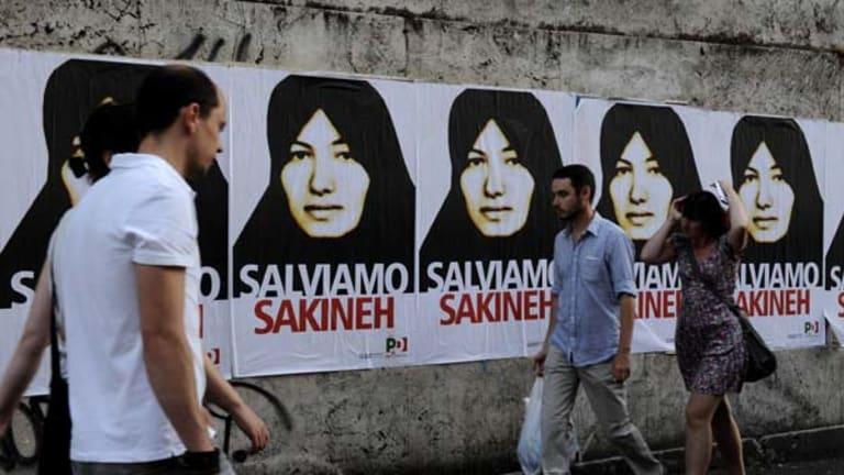 People walk by posters of Sakineh Mohammadi-Ashtiani.