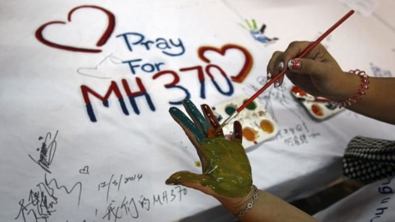 Hopeful ... A woman paints her palm with water colors during an event for passengers aboard a missing Malaysia Airlines plane, in Kuala Lumpur, Malaysia.