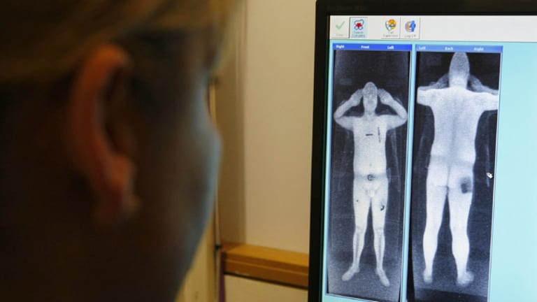 A security officer examines a computer screen showing a scan from a RapiScan full-body scanner in the UK.
