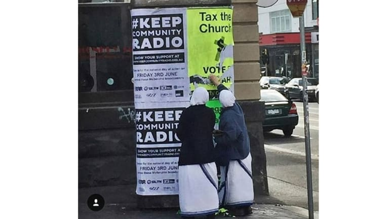 Two people dressed as nuns deface an Australian Sex Party poster in Melbourne.