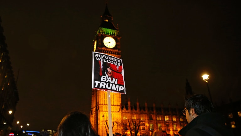 Demonstrators hold a banner during a protest against U.S President Donald Trump's controversial travel ban on refugees and people from seven mainly-Muslim countries, in London, Monday, Jan. 30, 2017. On Friday President Trump signed an executive order halting the US refugee programme for 120 days, indefinitely banning all Syrian refugees and suspended issuing visas for people from Iran, Iraq, Libya, Somalia, Sudan, Syria or Yemen for at least 90 days. (AP Photo/Alastair Grant)