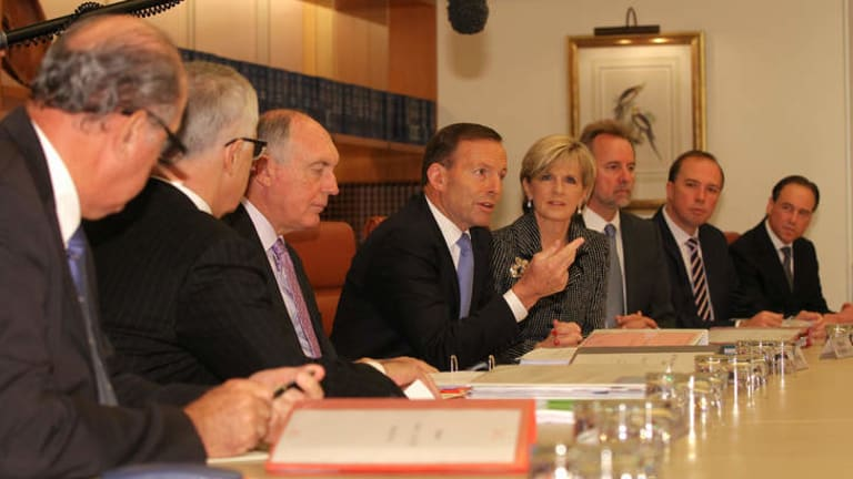 Prime Minister Tony Abbott address colleagues in a cabinet meeting. He has said that repealing the carbon tax is the priority for the government in negotiations with the incoming Senate.