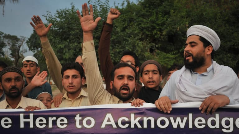 Pakistani residents shout slogans as they march behind a banner during a protest in Peshawar against the anti-Muslim cartoon exhibition in Garland, Texas.