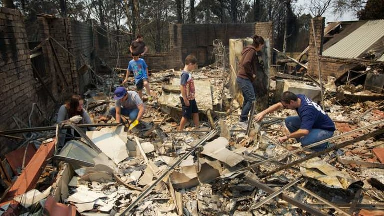 Aftermath of the Winmalee bushfire on Emma Pde. The Kozumplik family sifts through the rubble of what used to be their home for anything that can be salvaged.