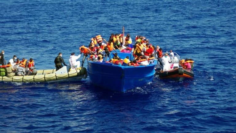 Italian Navy (left) help refugees to climb on their boat in the Mediterranean Sea on September 8. Thousands of migrants have been rescued by authorities in recent weeks.