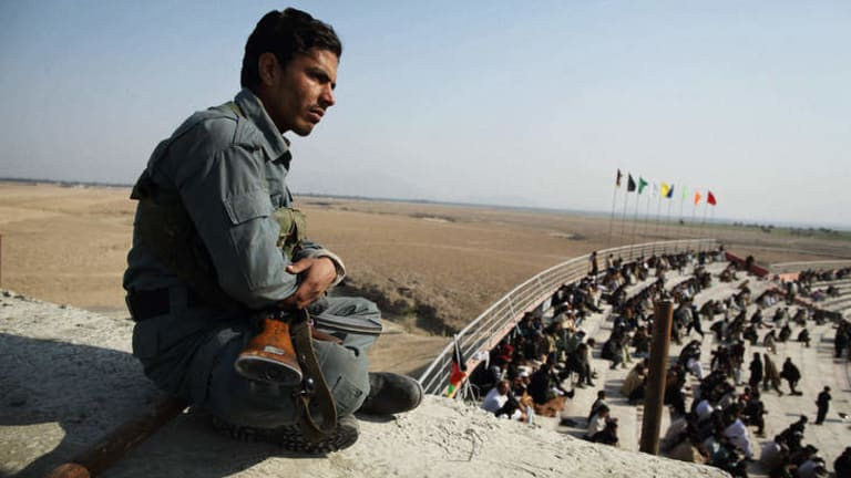 """Close watch: A policeman watches over the crowd at the Tajikistan-Afghanistan """"A"""" match in Jalalabad."""