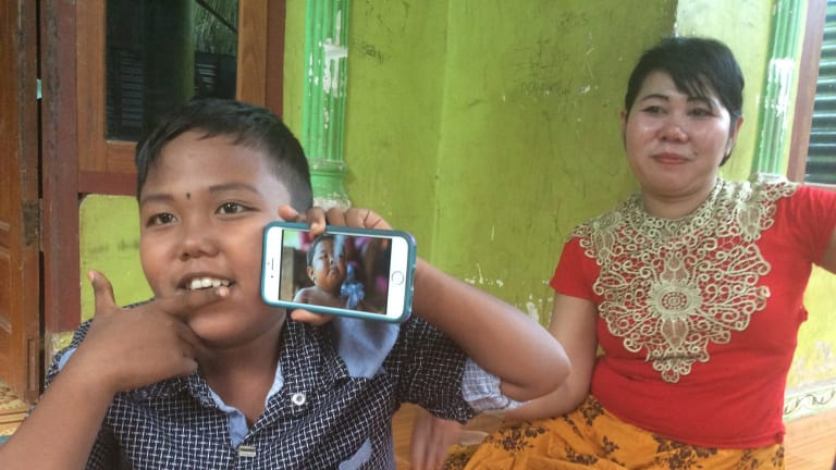 Aldi Rizal, with his mother Diana, quit smoking when he was four. He is  holding up a YouTube video of his younger smoking self.