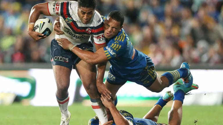Going nowhere: Michael Jennings of the Roosters is tackled by Will Hopoate of the Eels.
