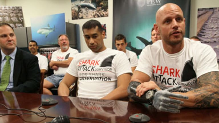 Paul de Gelder, right, speaks at a news conference in New York. He lost his hand in the attack.