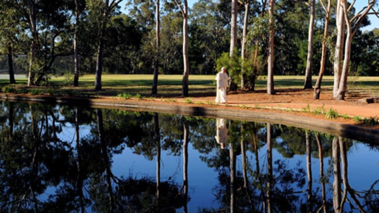 The Pope walks near a small lake at the Kenthurst Study Centre on the outskirts of  Sydney and (above)  with Cardinal George Pell and an unidentified bishop. Pictures: AP