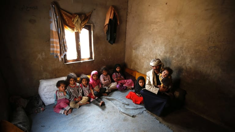 Faisal Ahmed, whose infant son, Udai Faisal, died of severe acute malnutrition, sits with his nine remaining children at his house in Hazyaz, Yemen.
