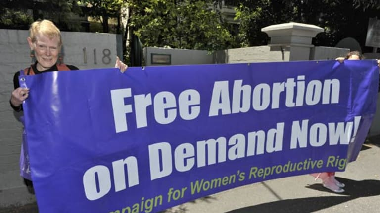 Debbie Brennan from the activist group Radical Women holds a banner outside the Fertility Control Clinic.