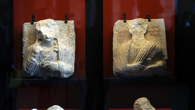"""Two defaced busts recovered from Palymra on display in Rome at an exhibition called """"Reborn from the Destructions""""."""