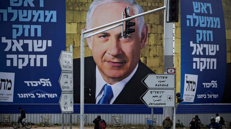 Last days … Israelis walk past a picture of the Israeli Prime Minister Benjamin Netanyahu, whose party is facing stiff opposition in the polls two weeks out from the election.