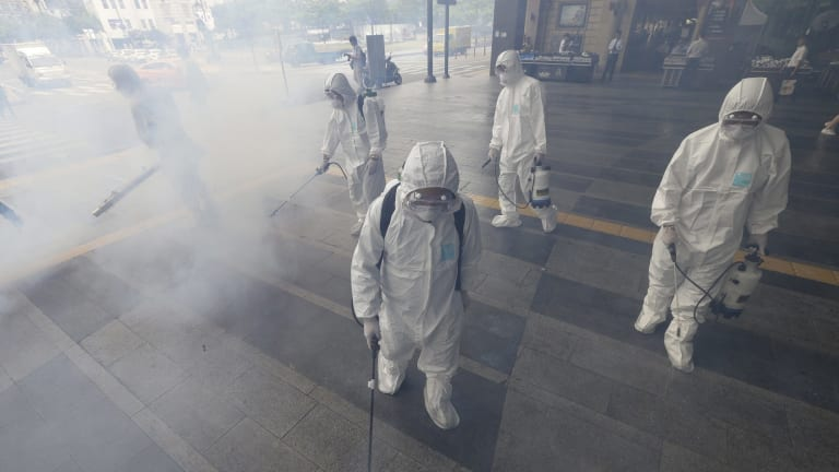 South Korean workers spay antiseptic solution outside a subway in an attempt to halt the spread of MERS in Seoul.