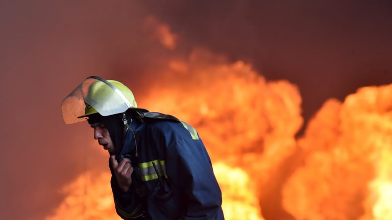 A Ukrainian firefighter retreats from the fire at the fuel depot outside Kiev.