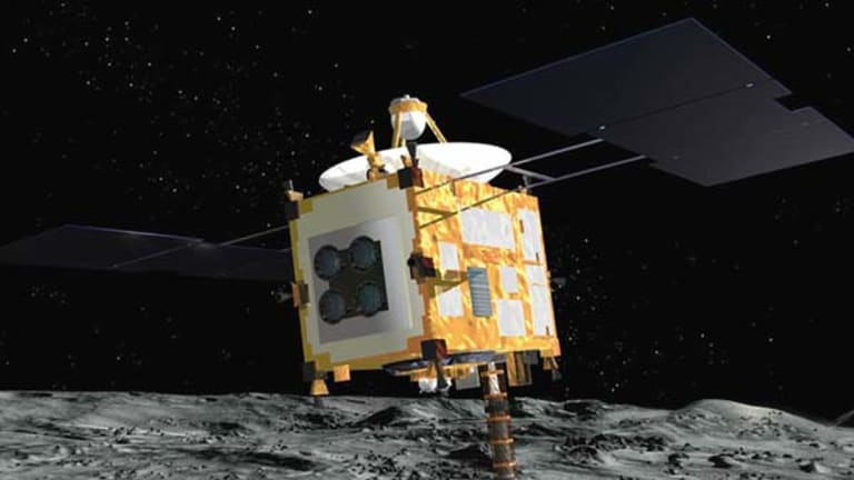 An artist rendering released by the Japan Aerospace Exploration Agency (JAXA) shows the Hayabusa probe collecting surface samples after landing on an asteroid.