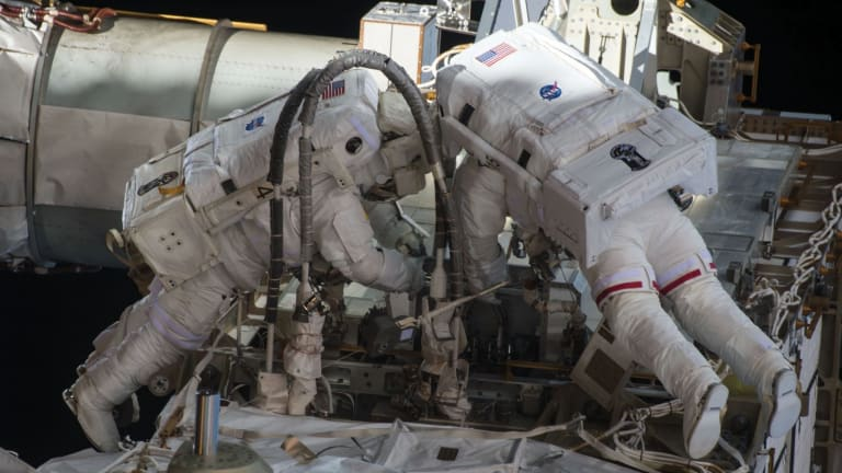 Scott Kelly (at left) undertaking a dangerous space walk outside the International Space Station.