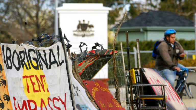 A cyclist passes the Aboriginal Tent Embassy.