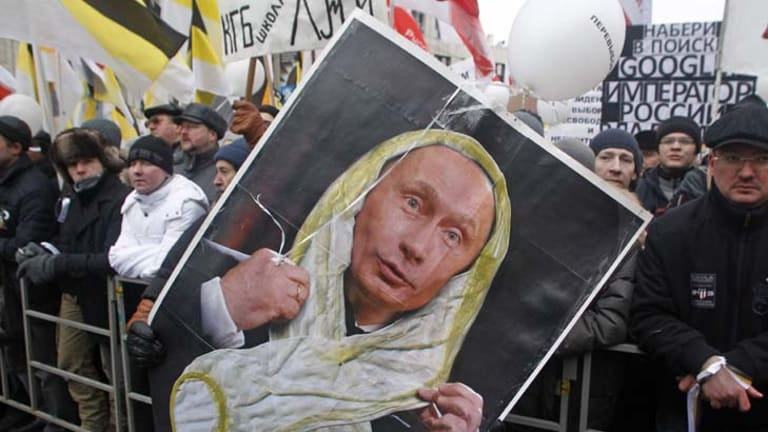 Scorned ... a protestor holds a poster showing Vladmir Putin in a white ribbon of the sort worn by protestors, which he has described as looking like condoms.