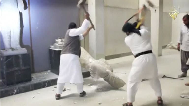 Men use sledgehammers on a toppled statue in a museum at a location said to be Mosul in this still image taken from an undated video.
