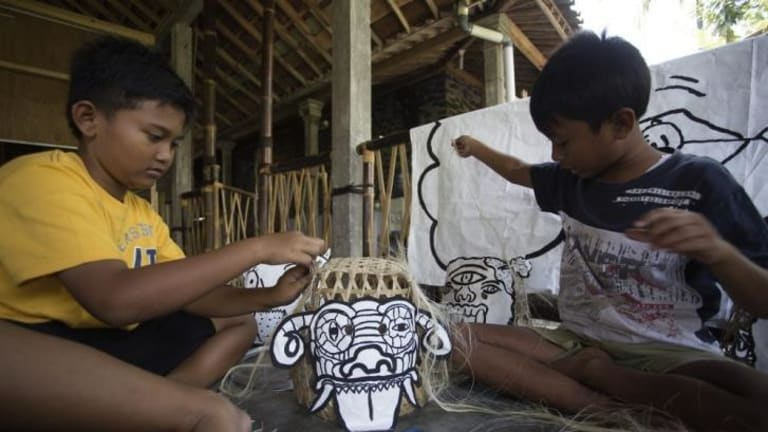 Children from a remote Indonesian community create puppets during a visit by members of Melbourne's Polyglot Theatre.