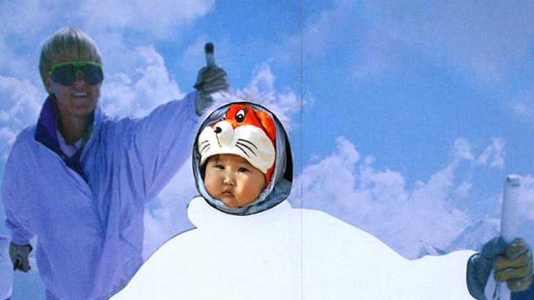 Precious Snowflakes ... a child pokes its head through a ski poster in Beijing.
