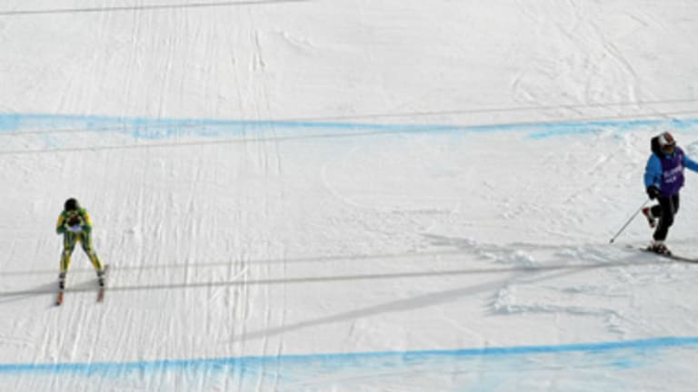 Close call ... Australia's Craig Branch narrowly misses a worker on the track during his downhill run in Whistler this week.