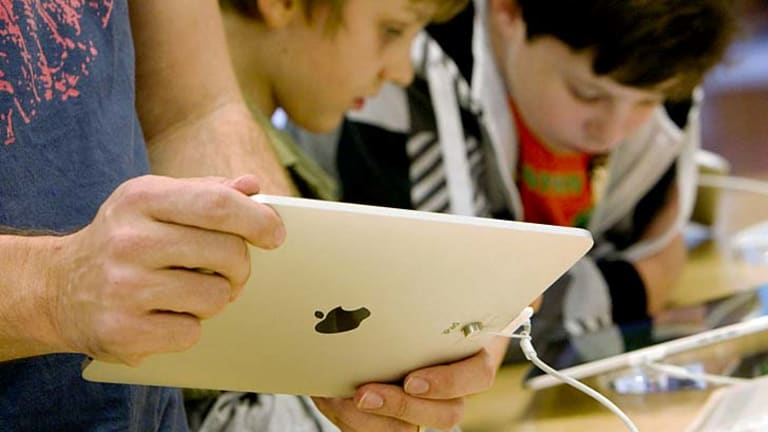 Children play with iPads in the Apple Store.