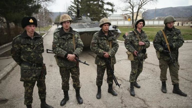 Ukrainian soldiers and a Ukrainian army tank stand just inside the gate at a Ukrainian military base that was surrounded by several hundred Russian-speaking soldiers in Crimea.