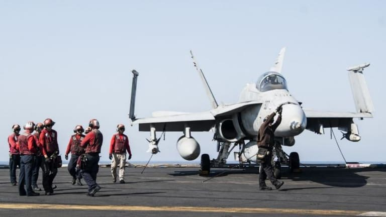 Ground crew on a US aircraft carrier prepare a fighter jet for take-off. Turkey has approved take-offs from bases close to the Syrian border.