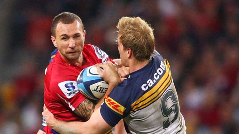 Reds' five-eighth Quade Cooper finds his way blocked by Brumbies' scrum-half Luke Burgess.