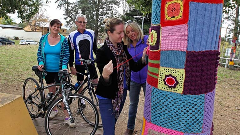 Community discord: (From left) Michelle and David Busch, Anna Hope and Belinda Cone with the patchwork tree trunks.