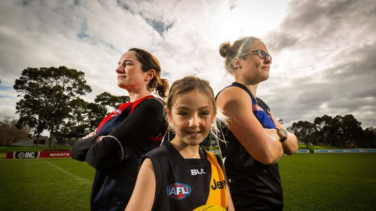 Catherine Nicholls, Molly Carr, 9, and Western Bulldogs player Emma Kearney at a footy clinic for women at Arden Street Oval.