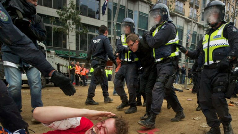 A bleeding protester shouts as riot police move in to remove Occupy Melbourne protesters from City Square.