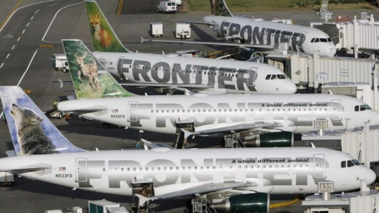 Frontier Airlines planes wait at their gates for the next batch of passengers at Denver airport.