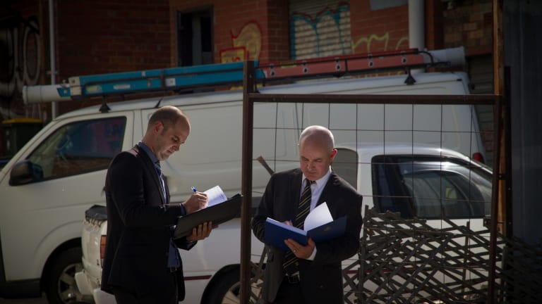 Paul Rowe (left) and Dave Butler typify the public's idea of homicide squad detectives, carrying bound folders and wearing darks suits.