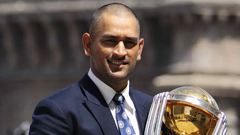 India captain Mahendra Singh Dhoni poses with the World Cup trophy.