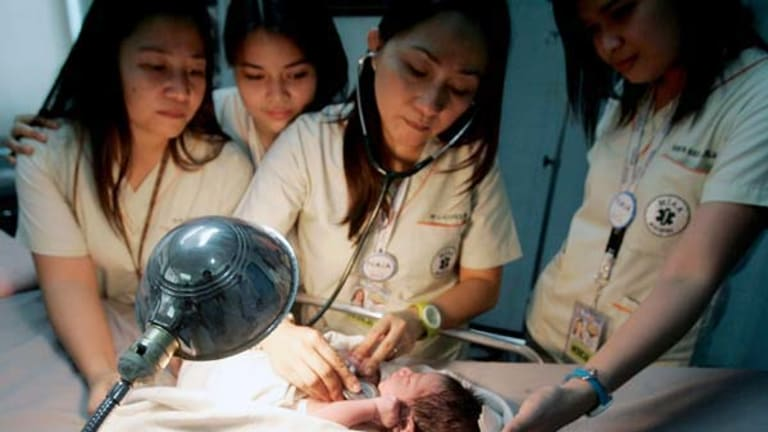 Doctors attend to a baby boy found by aircraft cleaners in a bin on a Gulf Air flight in Manila.