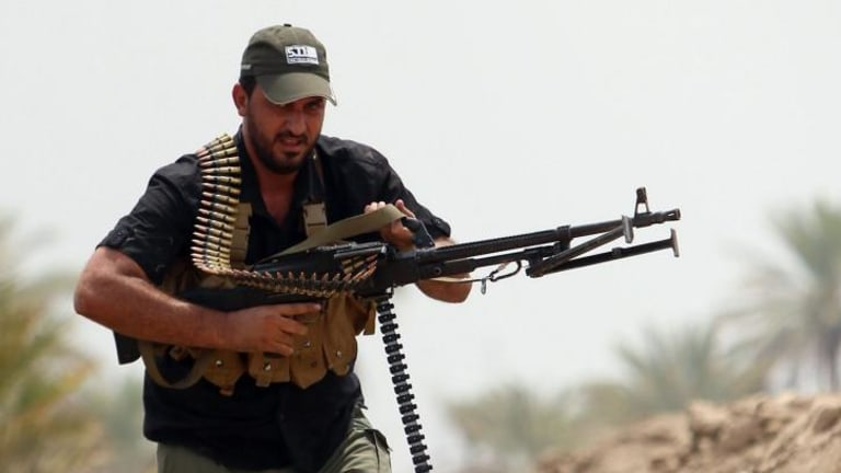 A Shiite Muslim fighter from the Saraya al-Salam  (Peace Brigades), tasked with defending the holy sites of Shiite Islam, takes position on the Jurf al-Sakhr front line against advancing Islamic State (IS) fighters.