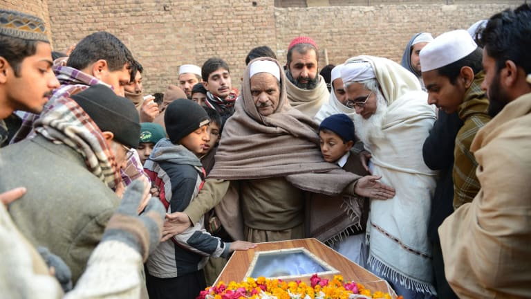 Pakistani mourners gather around a coffin during the funeral ceremony for victims of an attack by Taliban militants at an army-run school.