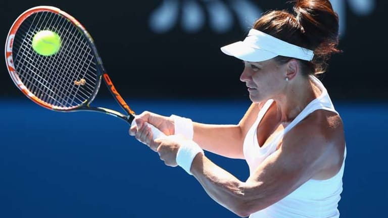 Casey Dellacqua plays a backhand against Zheng Jie of China.