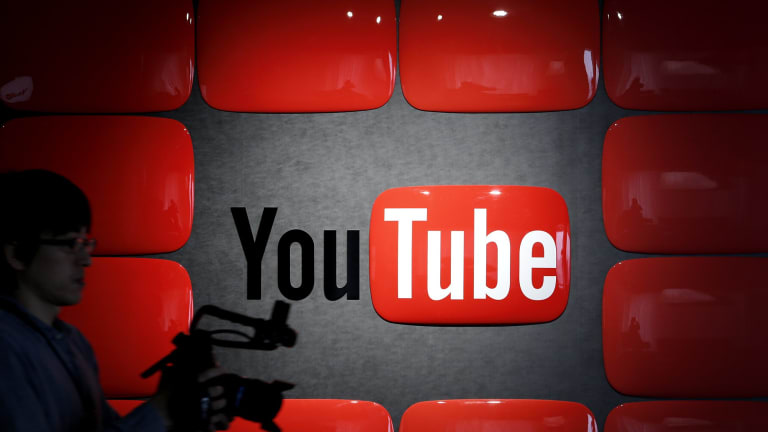 An employee holding recording equipment walks past Google Inc.'s YouTube logo displayed at the company's YouTube Space studio in Tokyo, Japan, on Saturday, March 30, 2013. In Japan, YouTube's biggest regional success story in Asia, the company is recruiting online stars to bolster its local-language channels with more-targeted original programming and higher production values.  Photographer: Kiyoshi Ota/Bloomberg