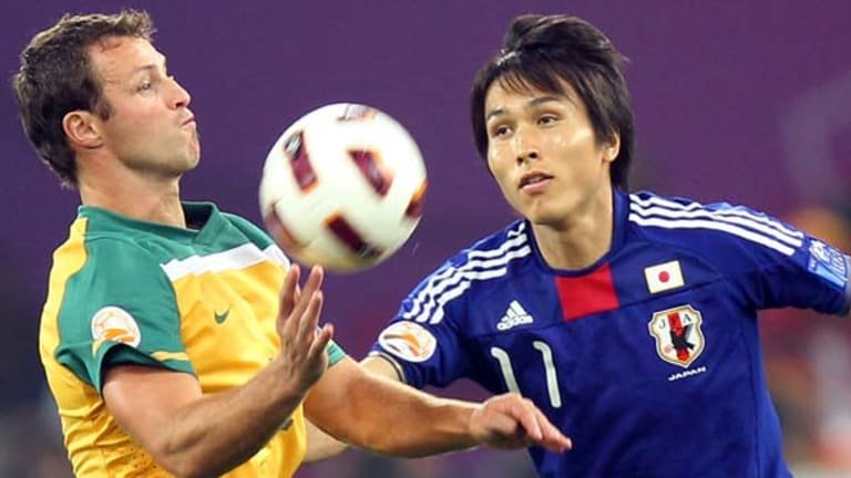 Australia's Lucas Neill fights for the ball against Japan's Ryoichi Maeda.
