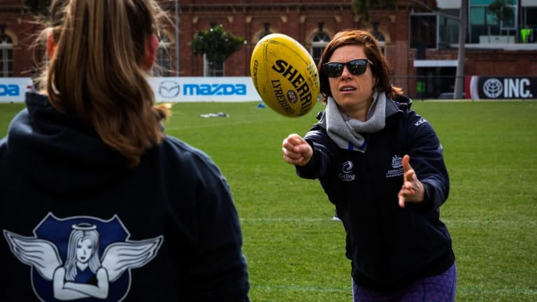 Bridie O'Donnell gets tips at a footy clinic for women at Arden Street Oval.