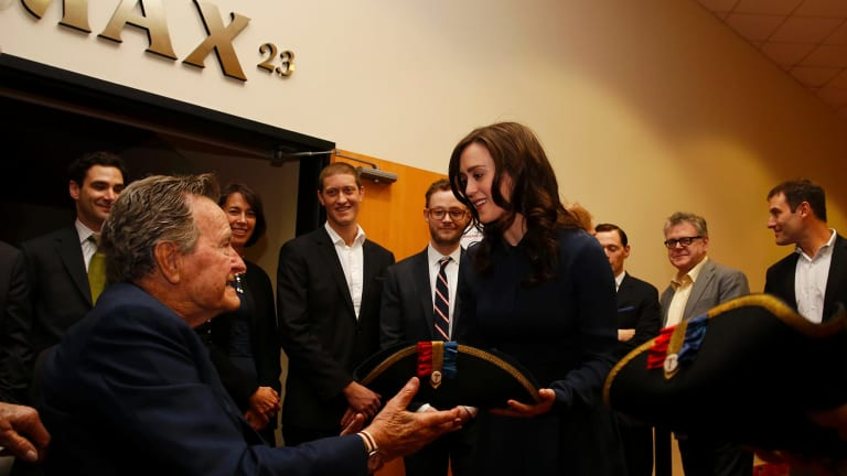 Former President George H.W. Bush, left, receives a tri-corner hat from actress Heather Lind, right, at a private screening in Houston, Texas.