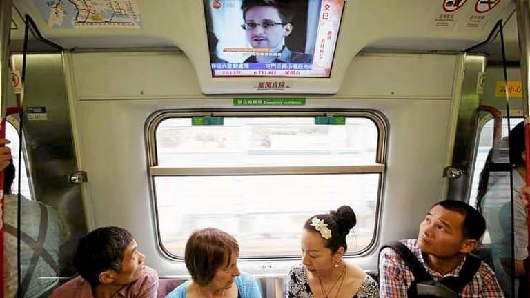 Passengers watch news on Edward Snowden on a train in Hong Kong.