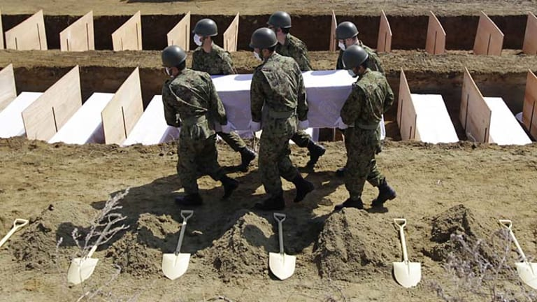 Japanese soldiers bury another victim in a mass grave.