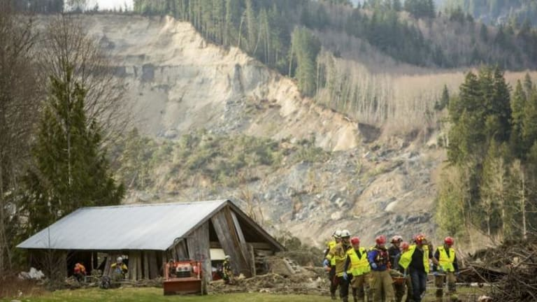 Rescue workers at one of the number of homes that were wrecked by the mudslide.